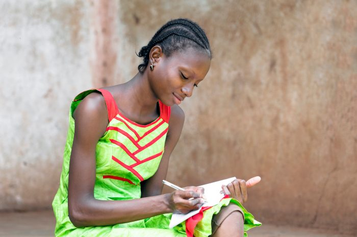 Gorgeous Black African Girl writing and drawing on her exercise book in a school using a pen. By buying this photo you help and support our social projects in Mali. Young schoolgirl education symbol.